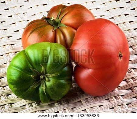 Arrangement of Red Green and Orange Raw Ripe Tomatoes with Stems closeup on Wicker background. Sort Fields Raf