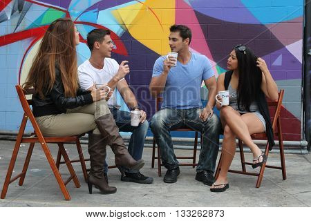Four friends sitting together during a brake drinking coffee.