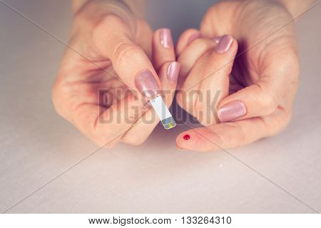 medicine diabetes glycemia health care and people concept - close up of female finger with blood drop and test stripe