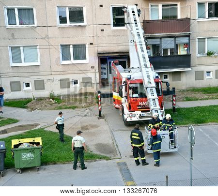 Bytca, Slovakia - June 4, 2016: Firefighters in action two of them get aboard into telescopic boom basket. Two police officers stand next to the fire truck