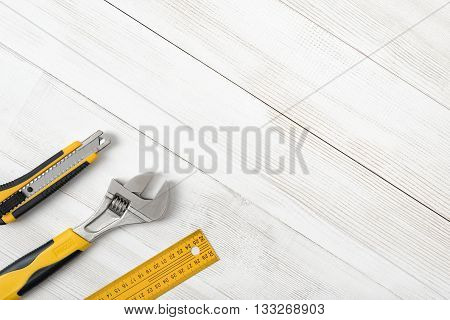 Construction tools including centimeter ruler, wrench and cutter placed in the right down corner on wooden surface with open space. Top view composition. Measurement. Fixing and cropping. Hand tool. Tools for carpentry work. Type of fastener. Mend and rep