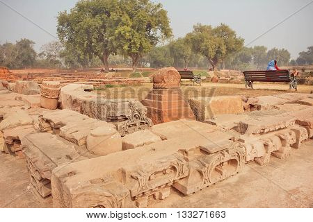 SARNATH, INDIA - JAN 5, 2016: Ruined Buddhist temple walls with patterns in green park with indian tourists on benches on January 5, 2016. Sarnath is where Gautama Buddha first taught the Dharma at 500 BC.