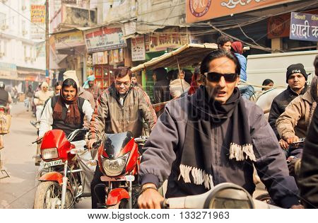 VARANASI, INDIA - JANUARY 4, 2016: Faces of drivers on motorcycles in traffic jam of urban indian of city on January 4, 2016. Varanasi urban agglomeration had a population of 1435113