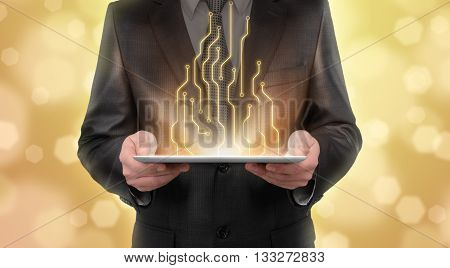 Businessman standing on blurry yellow background presenting new technologies of line diagram. New future. Thriving society. Digital presentation. Business staff. Digital tablet. Business concept.