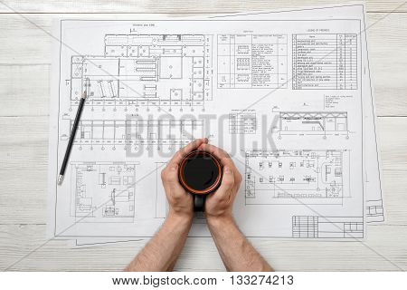 Close-up hands of man holding a cup of coffee over drawing layout in top view. Workplace of architect or constructor. Engineering work. Architect drawing. Uplifting mood. Coffee break. Conducive working environment. Increasing productivity in the mornings