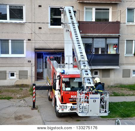 Bytca, Slovakia - June 4, 2016: Firefighter begin to uprise into telescopic boom basket of fire truck block of flats in background