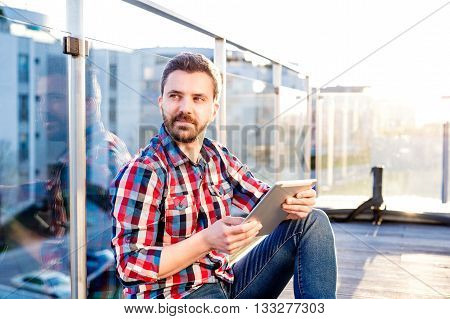 Young businessman in checked shirt and jeans writing on a tablet, sitting on the balcony