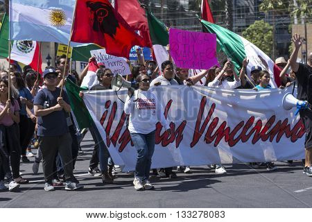 SAN DIEGO USA - MAY 27 2016: Hispanics against Donald Trump march behind a banner of unity outside a Trump rally in San Diego.