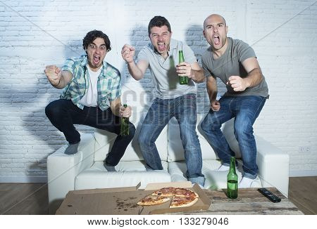 group of friends fanatic football fans watching soccer game on television celebrating goal jumping on couch screaming excited and ecstatic and crazy happy with beer bottles and pizza