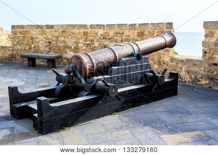 old bronze cannon in a fortress pointing to the sea from an embrasure