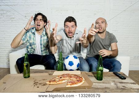 group of friends fanatic football fans watching soccer game on television with beer bottles and pizza suffering stress and crazy nervous on couch screaming and complaining