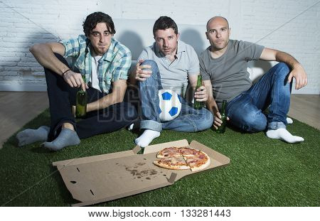 group of friends fanatic football fans watching soccer game on television with beers and pizza on grass carpet emulating stadium pitch looking nervous and stressed very focused on the match