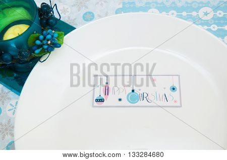 New Year Christmas Christmas tablecloth with a pattern of snowflakes with a plate of Christmas candy in red and white stripes and the background color of the flower blue and yellow candlestick copy space