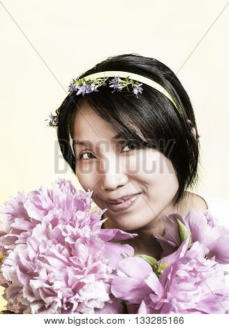 Pretty woman smelling the flowers. Studio portrait of pretty Korean woman smelling peony flowers.