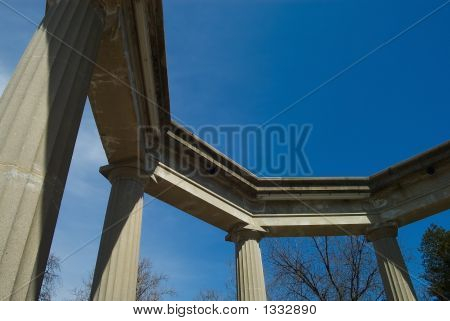poster of stone columns in a park on a sunny day