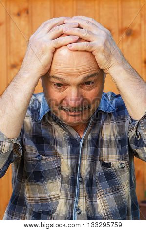 Elderly man suffering from a headache, putting his hand on his forehead
