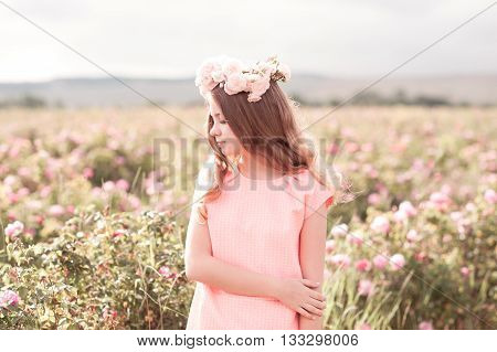 Beautiful teenage girl 14-16 year old wearing trendy dress and wreath with roses outdoors. Looking away.