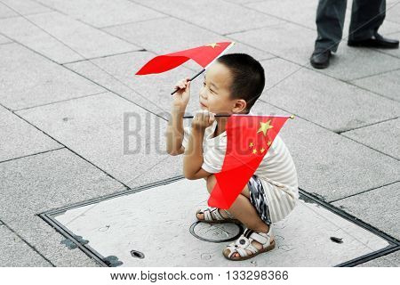 Beijing. China. - August 20, 2009 - The peoples of the world. Chinese boy with a Chinese flag The streets of China in August 20, 2009 in Beijing. China.