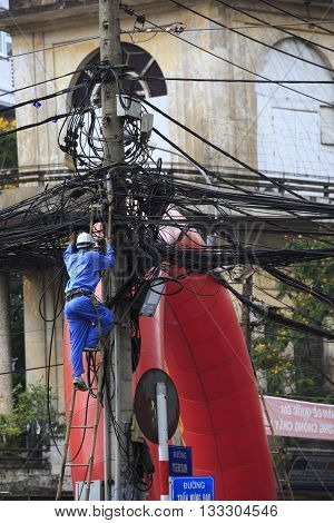 Man Working At Tangled Wires On Electric Poles