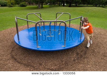 Young Boy Pushes A Merry-Go-Round
