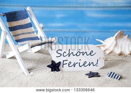Summer Label With German Text Schoene Ferien Means Happy Holidays. Blue Wooden Background. Card With Holiday Greetings. Beach Vacation Symbolized By Sand, Deck Chair And Shell.