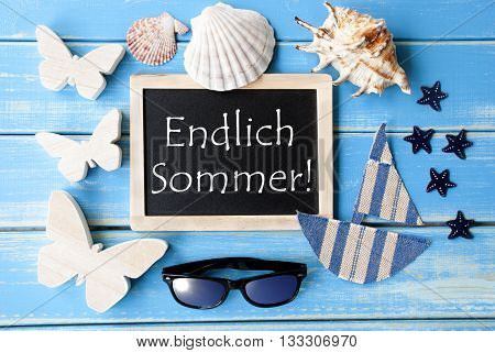 Flat Lay Of Chalkboard On Blue Wooden Background. Nautical Summer Decoration As Holiday Greeting Card. German Text Endlich Sommer Means Happy Summer