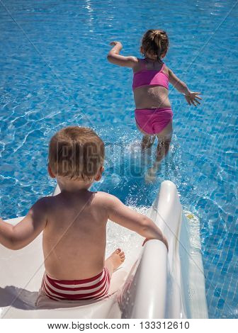 Cute two years old boy and four years old girl having fun on the small water slide in the outdoor swimming pool