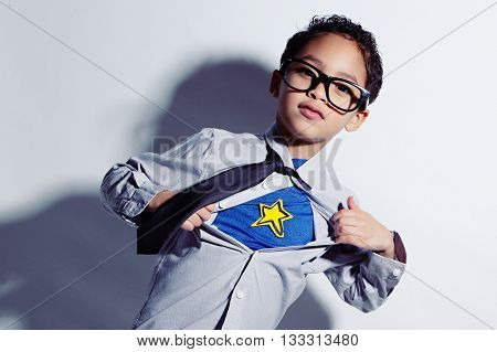 Undercover. Adorable mixed race boy ripping off his dress shirt to uncover his superhero costume underneath.