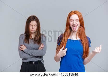 Two funny and depressed young women over white background