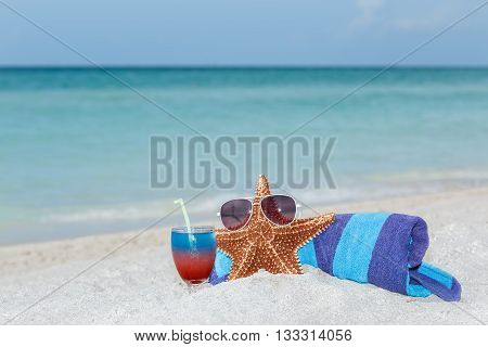 starfish standing on white sand beach between blue towel and colorful cocktail in wine glass against tranquil ocean and blue sky