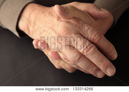 An older man grasps his hand on a black background with copy space.