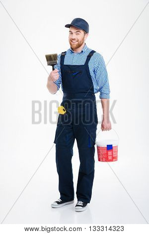 Happy bearded young man painter with can paint and brush standing and smiling