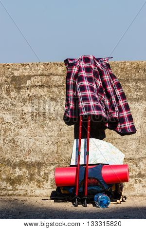 Trip travel relax survival concept. Plaid shirt with hiking gear. Outdoor equipment with bagpack on wall.