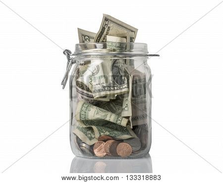 A tip jar or savings jar filled over the top with American coins and bills, on white with reflection.