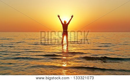 Silhouette of a man with raised arms in the sea water at sunset