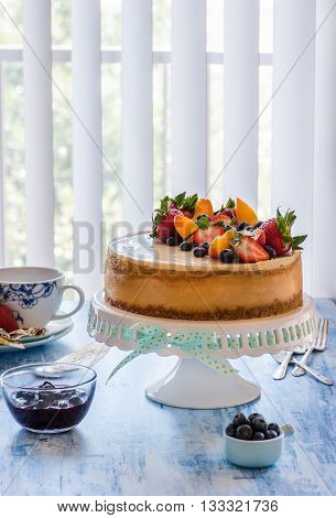 Caramel cheesecake with lemon curd on cakestand with blueberry sauce decorated with fresh berries. Selective focus vertical