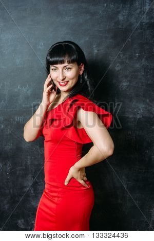 Beautiful young model woman in red dress posing over black slate background