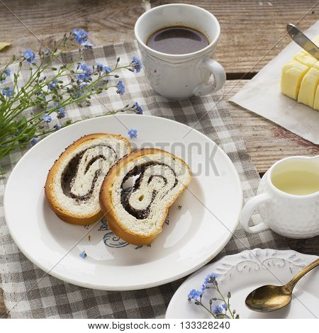 Traditional breakfast. Still life on a simple wooden background with slices of poppyseed roll with butter, a cup of coffee and fresh cream. View from above