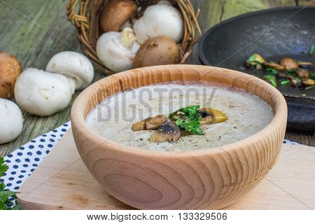 Creamy Champignon Soup in Wooden Bowl with Sautéed Champignon Mushrooms on cutting board