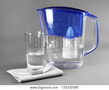 Filter and glass of water with napkin on grey background