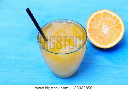Glass of orange juice with crushed ice on blue wooden table