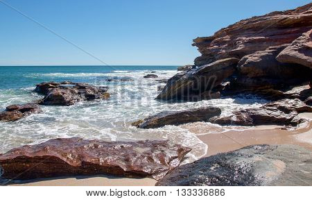 Turquoise Indian Ocean seascape with water rushing the sandstone rock outcropping at the secluded beach at Pot Alley under clear blue skies in Kalbarri, Western Australia.