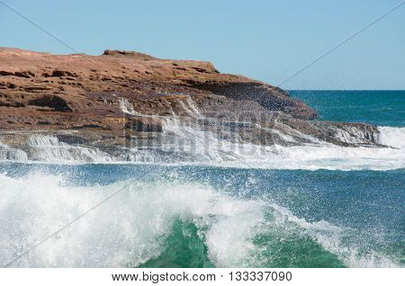 Indian Ocean wave spray and water rushing the sandstone outcropping at Pot Alley on a clear day in Kalbarri, Western Australia.