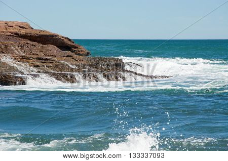 Indian Ocean waves cascading over sandstone rock outcropping at Pot Alley on a clear day in Kalbarri, Western Australia.