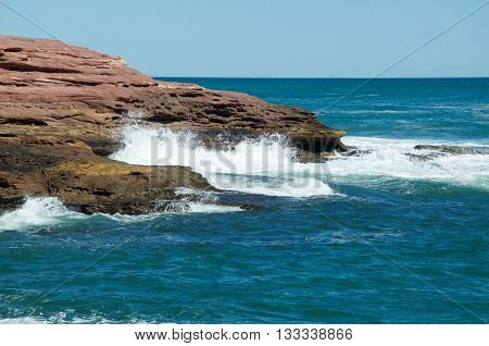 Turquoise Indian Ocean waters and sandstone rock outcropping at Pot Alley under blue skies in Kalbarri, Western Australia.
