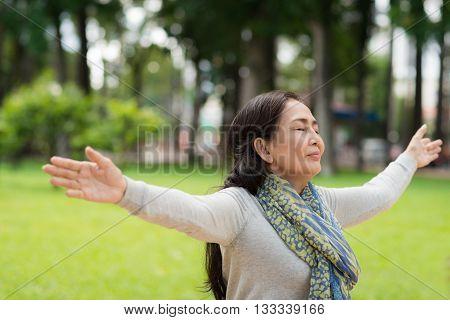 Vietnamese woman breathing fresh air in park