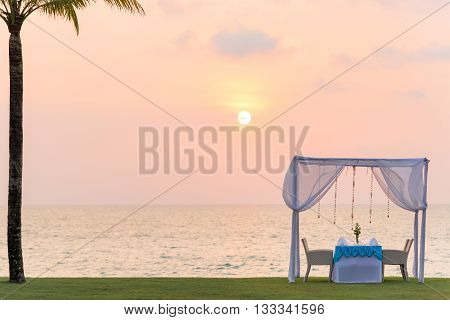 Romantic dinner setting on the beach at sunset. copy space.