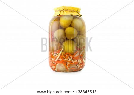 Homemade pickled green tomatoes with carrots and onions in glass jar with yellow paper wrapper. Homemade preserves, pickles. Jar of canned green marinated tomatoes isolated on white