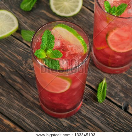 Two red cocktail with ice lime and mint in tall glass on dark wooden background. Top view with copy space poster