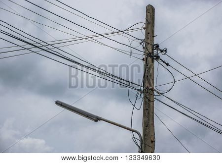 Electricity pole and street light complicated wiring With Dark Storm Clouds